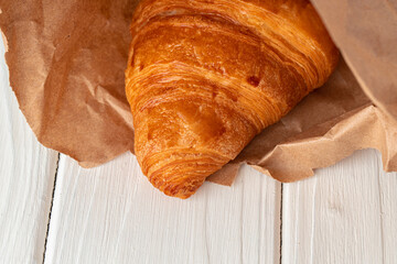 Fresh baked croissant on wooden table close up