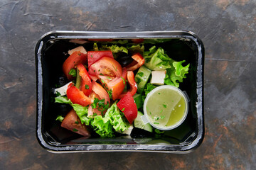 Diet salad with tomatoes and cucumbers and herbs. Healthy diet. Diet for weight loss. Healthy food delivery in plastic containers. High quality photo