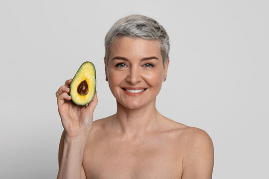 Essential Oils for Skincare And Beauty. Attractive middle-aged lady holding avocado half
