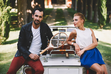 Happily married couple enjoying a beautiful day outdoors while leaning on their convertible antique car, handsome wealthy man and his gorgeous female posing outdoors, people spending time together