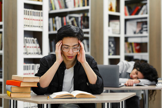 Two tired students studying in the university library
