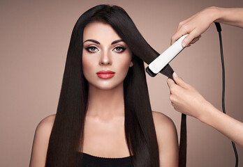 Hairdresser straightening long dark hair with hair irons. Beautiful woman with long straight hair....