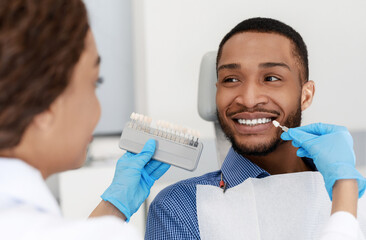 Dentist choosing filling shade for smiling patient