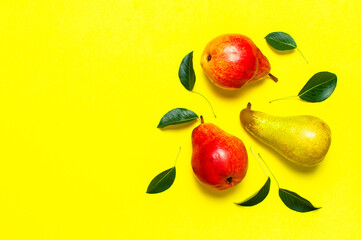 Wall Mural - Creative background with pears and green leaves. Juicy ripe fresh green and red pears on yellow background flat lay top view copy space. Fruit background, organic healthy food. Harvest concept