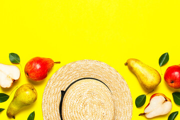 Wall Mural - Creative background with pears and green leaves. Ripe fresh green red pears, straw hat on yellow background flat lay top view copy space. Fruit background, organic healthy food. Harvest concept