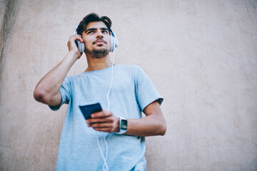 Cheerful hipster guy in modern headphone listening new song from internet radio website using...