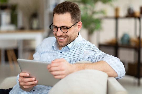 Happy man using digital tablet sitting on sofa