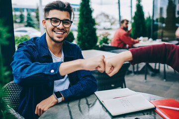 Cropped image of hipster guy in spectacles bumping fists with female colleague satisfied with making agreement sitting at cafe terrace, cheerful young man happy about completing task in cooperation