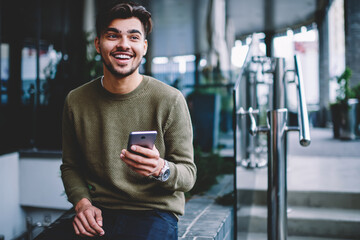Happy bearded hipster guy excited with good news receiving message on smartphone sitting on urban...