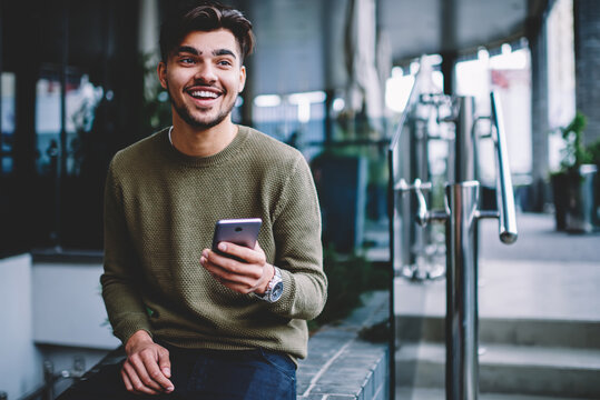 Happy bearded hipster guy excited with good news receiving message on smartphone sitting on urban settings, cheerful handsome man satisfies with mobile tariffs for calls and messages chatting on phone