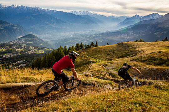 CRANS MONTANA, SWITZERLAND. Two mountain bikers riding a twisty trail in the purpose built bike park. Snow capped mountains and evening mist in the Sion valley behind.