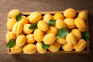fresh ripe apricots with leaves in a box on a wooden table