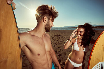 caucasian  fit, sexy couple, talking on a beach, holding surfboards. ultraviolet radiation, protection concept