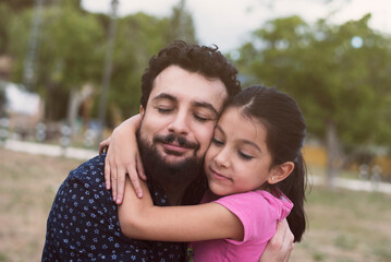 Father and little daughter big hug in outdoors image in park