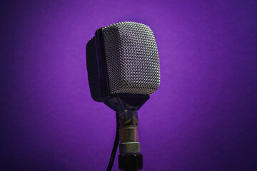 Classic dynamic microphone on a purple background. Vintage style music concept