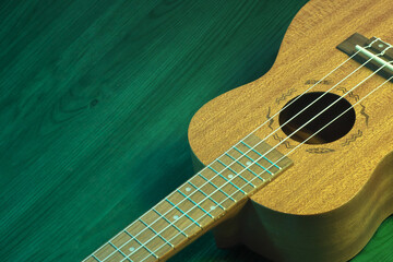 Studio shot of a ukulele on a green wooden table. A music background with copyspace