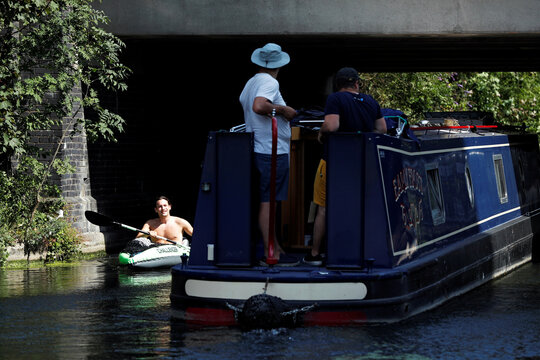Man in a canoe passes a canal boat on Grand Union Canal in London