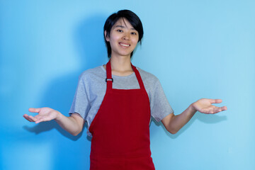 Friendly young asian male waiter with red apron