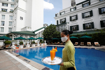 A woman wearing a protective mask carries glasses of fruit juice by the swimming pool of the Sofitel Legend Metropole hotel in Hanoi