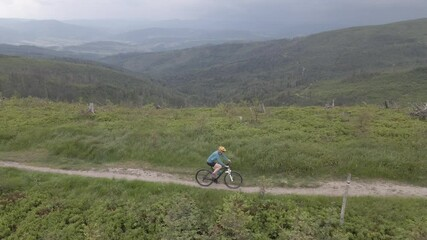 Wall Mural - Aerial shot of  mountainbike woman riding on bike in summer mountains landscape. Woman cycling MTB.