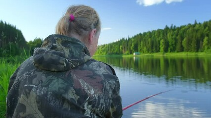 Wall Mural - Woman fishing. Eldery woman angler fishing on the summer picturesque lake during calm evening