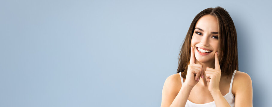 Bright image of young brunette woman showing smile, in casual smart clothing, over grey background. Caucasian model - optimistic, positive, happy feeling concept. Copy space for some text.