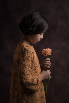 Young girl in yellow dress seen en profile looking at yellow flower in painterly rembrandt studio style