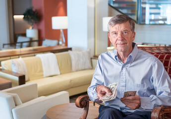 Senior caucasian man holding some US dollar bills as if handing them to the viewer. Composite into upmarket lounge of hotel or cruise ship