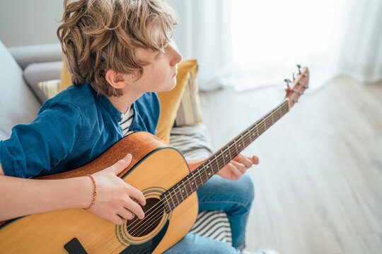 Top angle view at Preteen boy playing acoustic guitar dressed casual jeans, blue shirt sitting on the cozy sofa at the home living room and thinking about something. Music education concept image.