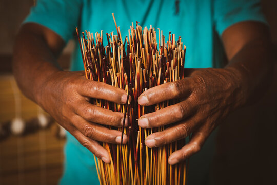 Detail of artisan's hand and reed straws for production of traditional handicraft mat made of dry reed in a local community of Garopaba, Brazil.