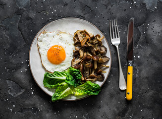 Healthy breakfast, brunch - fried egg with wild mushrooms and green salad on a dark background, top view