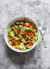 Seafood and vegetables salad. Salad with tomatoes, cucumbers, bell peppers and canned mussels on a grey background, top view