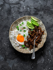 Spicy roasted beef, rice, fried egg and avocado - delicious asian style lunch on a dark background, top view