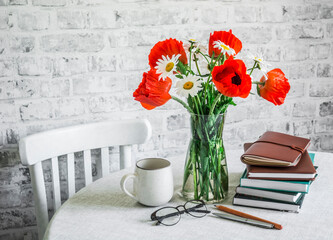 Cozy interior home concept. Bouquet of poppies, daisies, stack of books, cup of tea on a table in a light room