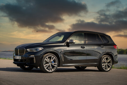 BMW X5 G05 near river at the sunset
