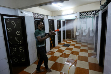 A volunteer sprays disinfectant in bathrooms inside a mosque as it is prepared for prayer after being reopened, following the outbreak of the coronavirus disease (COVID-19), in Cairo