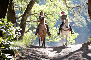 Two women riding horses toward camera with backlit leaves