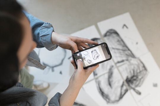 Artist photographing drawing with phone