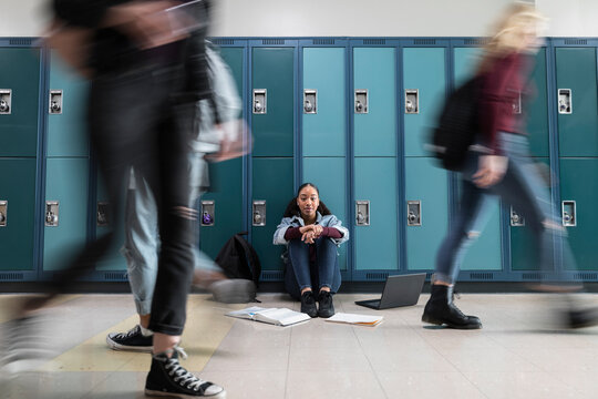Portrait high school girl student studying at lockers in corridor