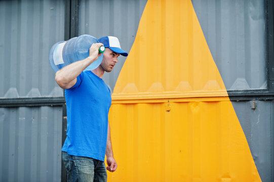 Delivery man carrying water bottle on shoulder.