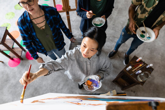 Woman painting in art class high angle