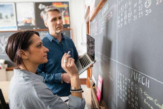 Man and woman planning dates on blackboard