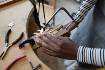 Woman sawing metal in craft studio
