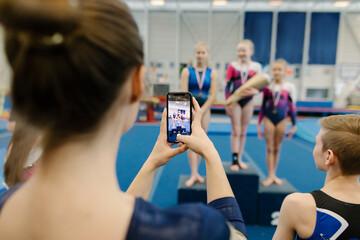 Girl photographing gymnasts on podium