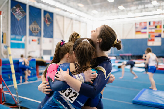 Gymnasts hugging in gymnasium