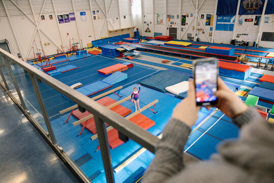Woman filming girl on balance beam in gym