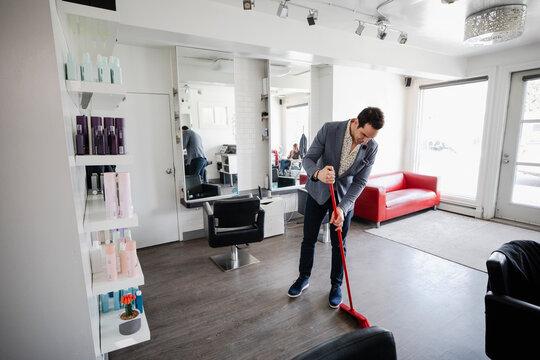 Business owner sweeping floor of hair salon