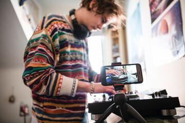 Young man filming himself djing in bedroom
