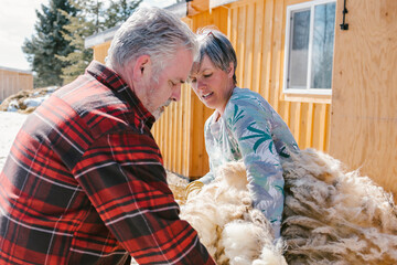 Sheep farmers holding bundle of wool outside sunny barn