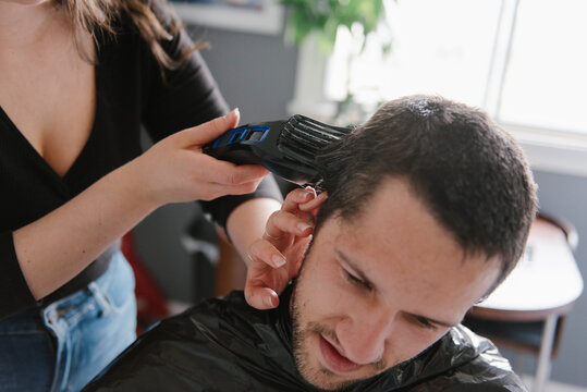 Woman cutting man's hair with clippers